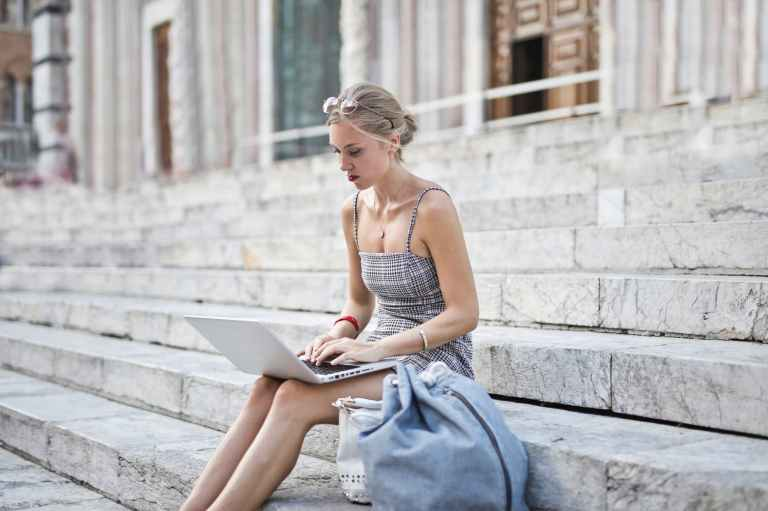women in grey spaghetti strap dress sitting o n concrete stairs while placing laptop on her lap