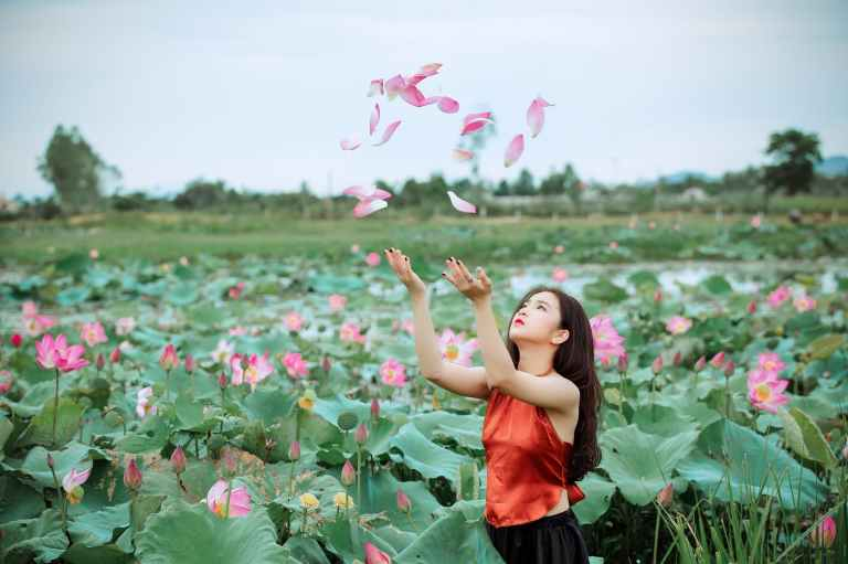 woman throwing pink petals