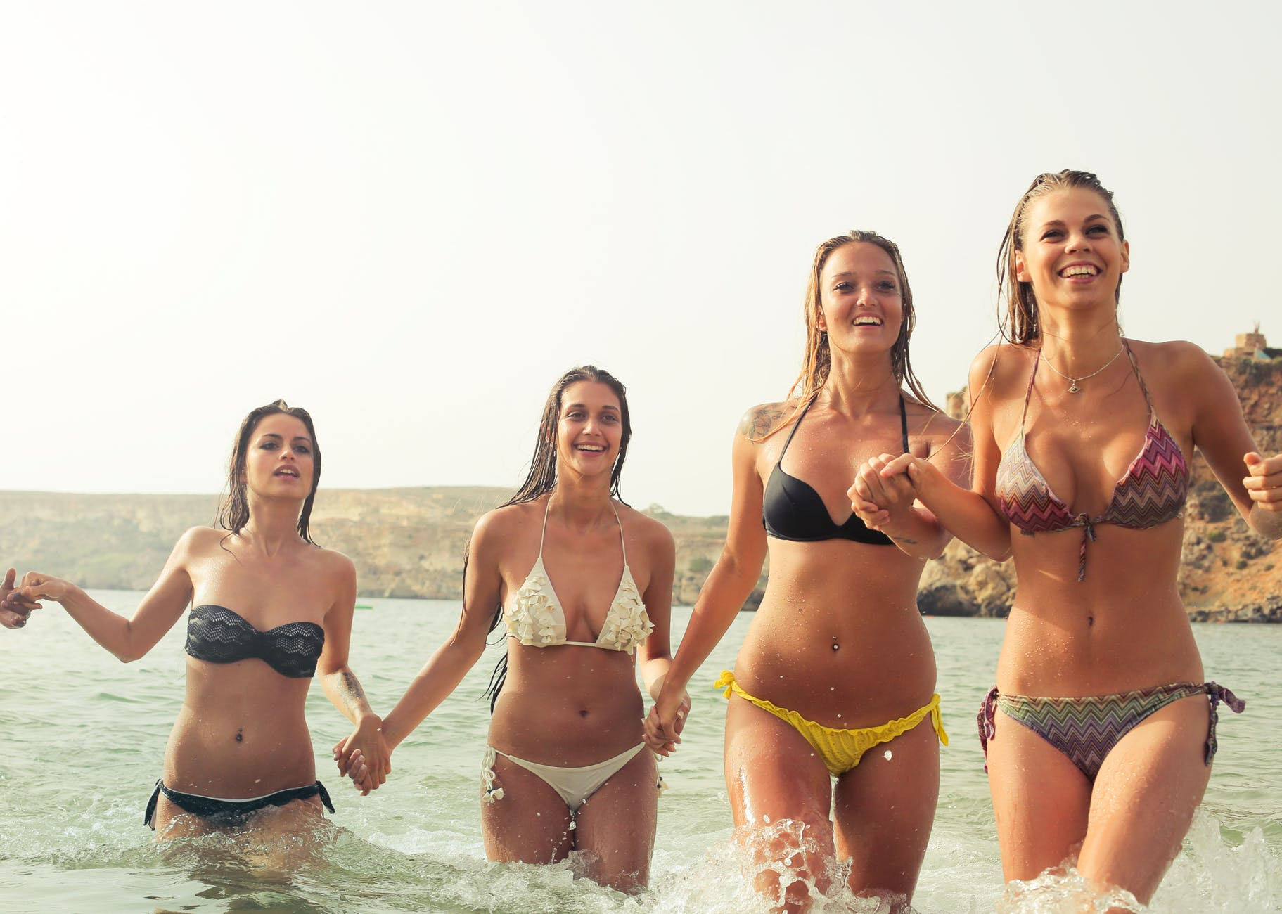group of woman wearing bikini on body of water